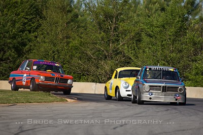 A 1969 BMW 2002 Tii leads a 1964 Porsche 356 and a 1969 BMW 2002 through 3.