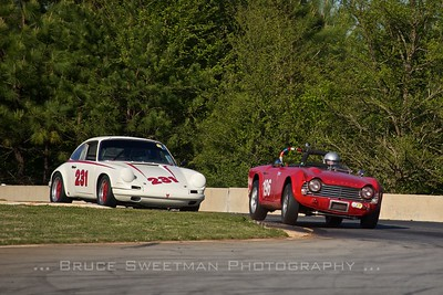 A Porsche 911 follows a 1964 Triumph TR-4 through Turn 3.