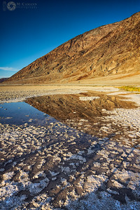 Death Valley National Park, California. Thankgiving break.  The hills and sky reflected in an alkali pool at Badwater Basin.