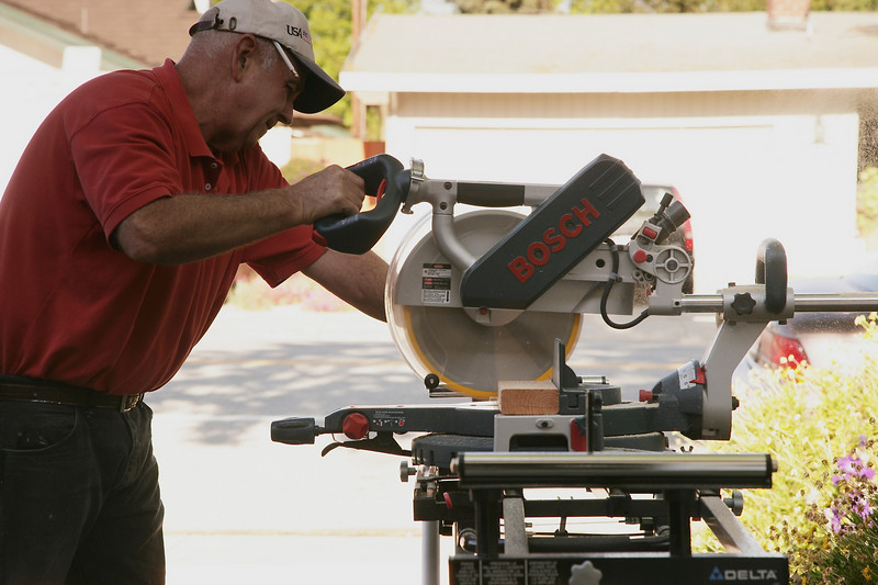 Jerry uses his circular saw to cut more wood.