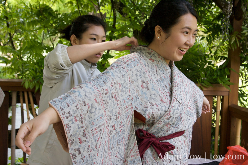 Yuki helps Angela with her kimono and obi.