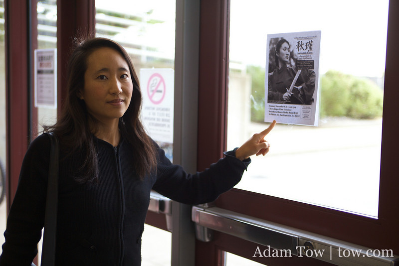 Rae next to an Autumn Gem screening poster at City College.