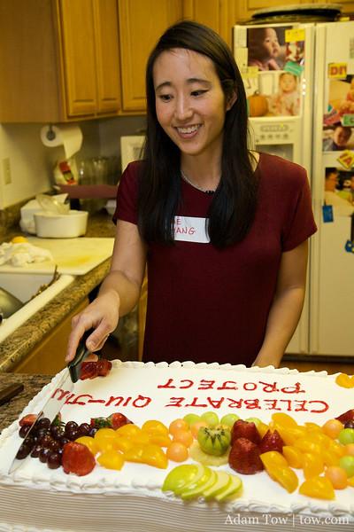 Rae cutting the Qiu Jin Project celebratory cake.