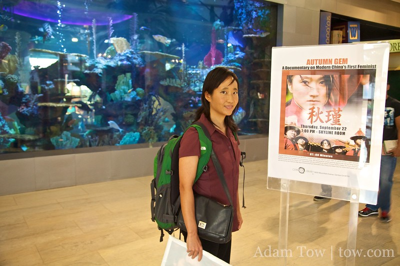 Rae stands in front of an Autumn Gem poster (and giant aquarium) at the Cerritos Public Library.