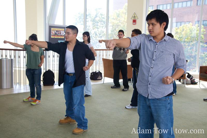 UMass students punching during wushu basics demonstration.