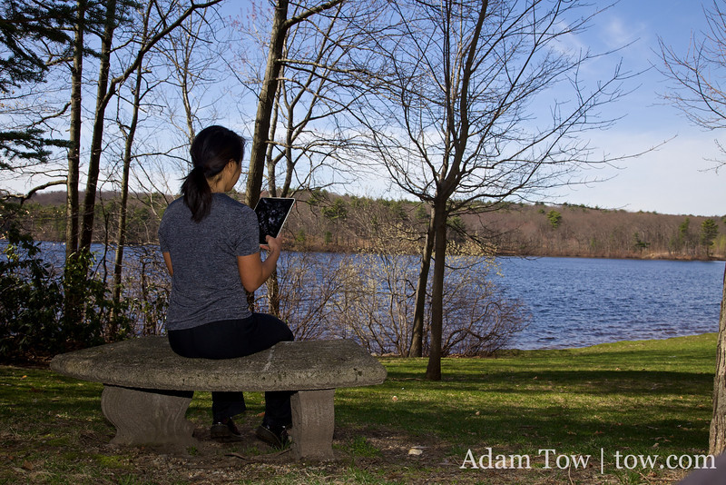 Rae reads the iPad on a bench near Lake Waban at Wellesley College.