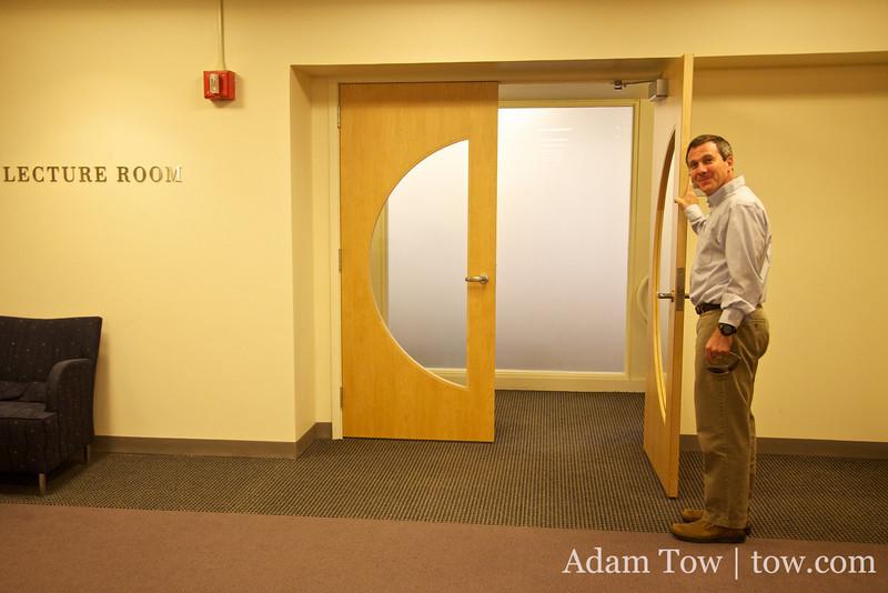 Professor Giesrch holds open the door to the screening room.