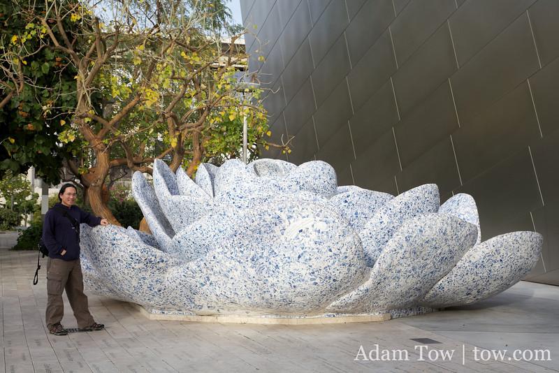 Adam next to a giant flower sculpture in LA.