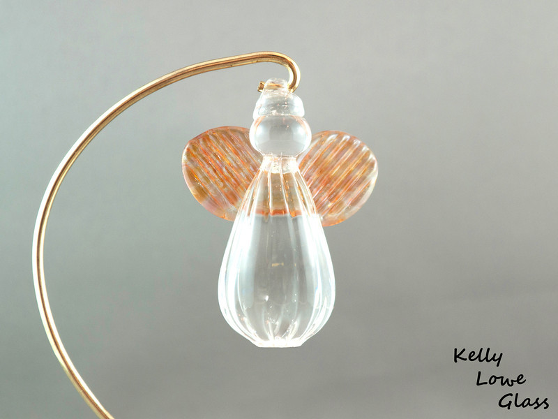"""Hanging Glass Angel - Apricot  Height: Approx 8cm (3.15"""") Across the Wings: Approx 5.5cm (2.17"""") Depth: Approx 3cm (1.19"""") Weight: Approx 85g (0.19 lbs)  *Brass hanger in pictures is not included  Please note: as each piece begins its life as molten glass and is blown/sculpted by hand into the final product, individual pieces might have slight variations in size and/or appearance. Please rest assured however that the standard of quality is quite high, and no substandard pieces will be sold."""