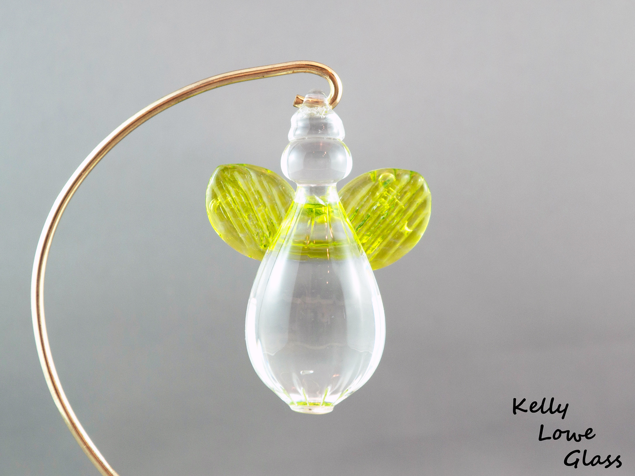 """Hanging Glass Angel - Lime Green  Height: Approx 8cm (3.15"""") Across the Wings: Approx 5.5cm (2.17"""") Depth: Approx 3cm (1.19"""") Weight: Approx 85g (0.19 lbs)  *Brass hanger in pictures is not included  Please note: as each piece begins its life as molten glass and is blown/sculpted by hand into the final product, individual pieces might have slight variations in size and/or appearance. Please rest assured however that the standard of quality is quite high, and no substandard pieces will be sold."""