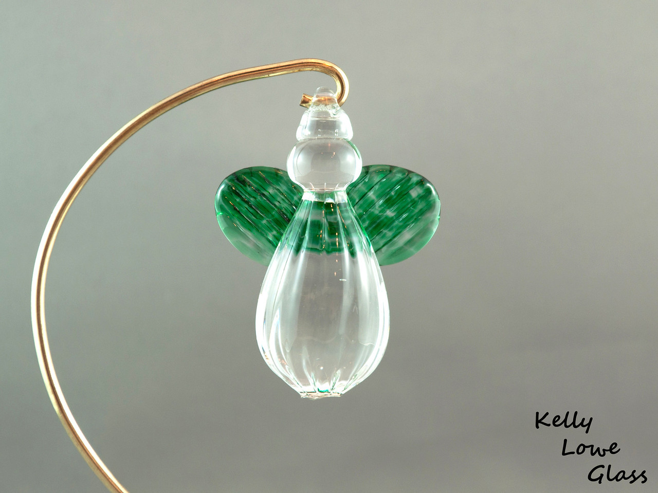 """Hanging Glass Angel - Green  Height: Approx 8cm (3.15"""") Across the Wings: Approx 5.5cm (2.17"""") Depth: Approx 3cm (1.19"""") Weight: Approx 85g (0.19 lbs)  *Brass hanger in pictures is not included  Please note: as each piece begins its life as molten glass and is blown/sculpted by hand into the final product, individual pieces might have slight variations in size and/or appearance. Please rest assured however that the standard of quality is quite high, and no substandard pieces will be sold."""