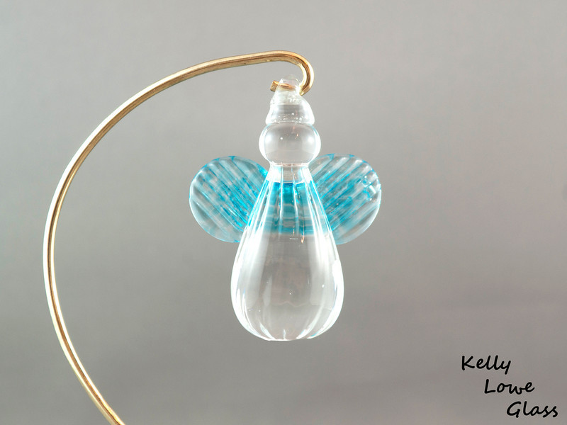"""Hanging Glass Angel - Light Blue  Height: Approx 8cm (3.15"""") Across the Wings: Approx 5.5cm (2.17"""") Depth: Approx 3cm (1.19"""") Weight: Approx 85g (0.19 lbs)  *Brass hanger in pictures is not included  Please note: as each piece begins its life as molten glass and is blown/sculpted by hand into the final product, individual pieces might have slight variations in size and/or appearance. Please rest assured however that the standard of quality is quite high, and no substandard pieces will be sold."""