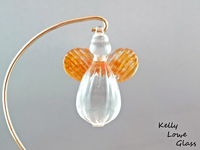 "Hanging Glass Angel - Gold Topaz  Height: Approx 8cm (3.15"") Across the Wings: Approx 5.5cm (2.17"") Depth: Approx 3cm (1.19"") Weight: Approx 85g (0.19 lbs)  *Brass hanger in pictures is not included  Please note: as each piece begins its life as molten glass and is blown/sculpted by hand into the final product, individual pieces might have slight variations in size and/or appearance. Please rest assured however that the standard of quality is quite high, and no substandard pieces will be sold."