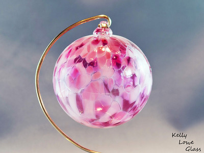 "Christmas Ornaments:  Individually hand blown using the same methods glassblowers have used since antiquity, these ornaments are a holiday classic  just like great great great great great grandma may have had.   I make these Christmas balls in a variety of colours, (see the link below for more examples) including the pink one pictured here. Each ornament begins life as liquid glass in a special glassblowing furnace, from which it's pulled and blown by mouth into a hollow sphere. During this process colour is added, which melts and is allowed to flow and combine throughout ornament, making each ball truly one of a kind: the color will never mix in the same way twice. While the piece is still hot a small glass loop is added to the top to make for easy hanging from a Christmas Tree or any other place one could wish to hang it, and finally it is slowly cooled over the course of 24 hours in a special glass kiln to ensure the glass is very strong and will last a lifetime.  Diameter - Approx 9.5cm (3.75"") Weight: Approx 78g (0.17 lbs)"