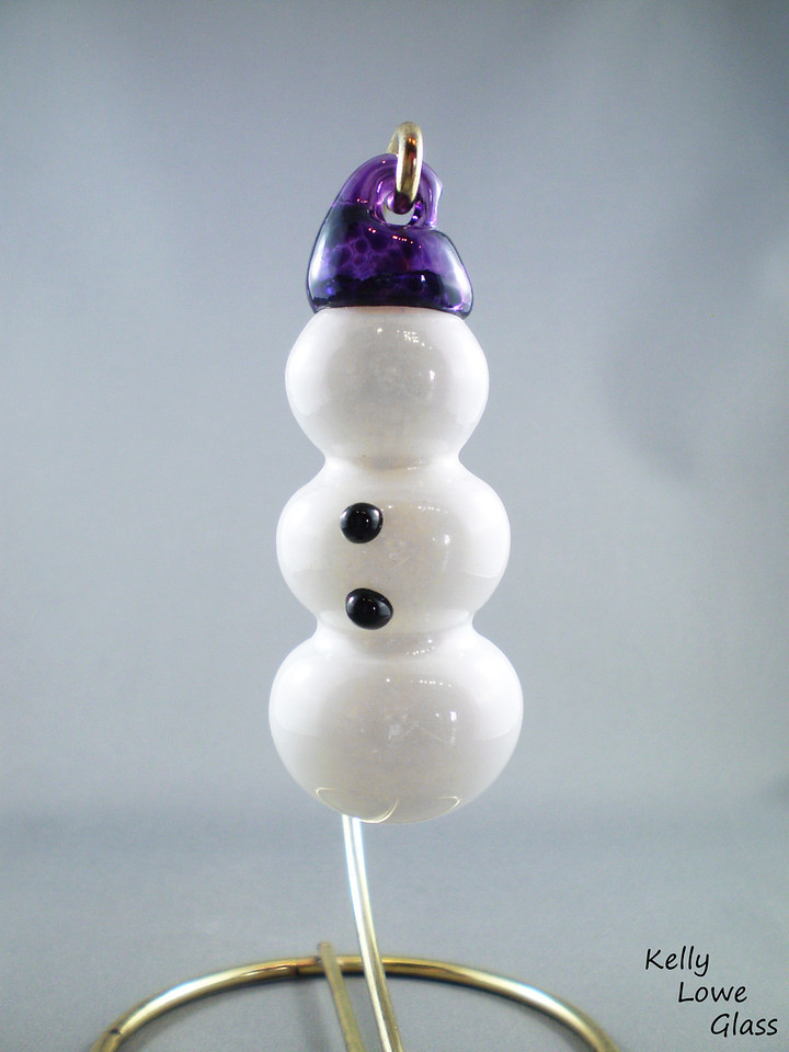 """Glass Snowman Decoration:  These hand sculpted snowmen are faceless yet fashionable, with two timeless buttons and a hat crafted just for him. Also, a fancy hanging string, and we all know how stylish those are.  Height: Approx 8.5cm (3.35"""") Wide: Approx 3.5cm (1.38"""") Weight: Approx 95g (0.21 lbs)"""