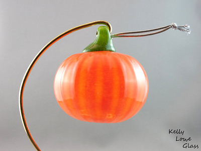 "Blown Glass Pumpkin:  A blown glass pumpkin complete with hanger, made originally for a Halloween showcase as a small, inexpensive gift item. They proved popular and I enjoyed making them, and so I decided to make them a regular seasonal feature.  Height - Approx 7.5cm (3"") Width - Approx 7cm (2.75"") Weight: Approx 78g (0.17 lbs)  *Brass hanger in pictures is not included  Please note: as each piece begins its life as molten glass and is blown/sculpted by hand into the final product, individual pieces might have slight variations in size and/or appearance. Please rest assured however that the standard of quality is quite high, and no substandard pieces will be sold."