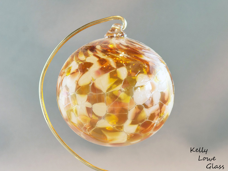 """Christmas Ornaments:  Individually hand blown using the same methods glassblowers have used since antiquity, these ornaments are a holiday classic  just like great great great great great grandma may have had.   I make these Christmas balls in a variety of colours, (see the link below for more examples) including the topaz and beige one pictured here. Each ornament begins life as liquid glass in a special glassblowing furnace, from which it's pulled and blown by mouth into a hollow sphere. During this process colour is added, which melts and is allowed to flow and combine throughout ornament, making each ball truly one of a kind: the color will never mix in the same way twice. While the piece is still hot a small glass loop is added to the top to make for easy hanging from a Christmas Tree or any other place one could wish to hang it, and finally it is slowly cooled over the course of 24 hours in a special glass kiln to ensure the glass is very strong and will last a lifetime.  Diameter - Approx 9.5cm (3.75"""") Weight: Approx 78g (0.17 lbs)"""