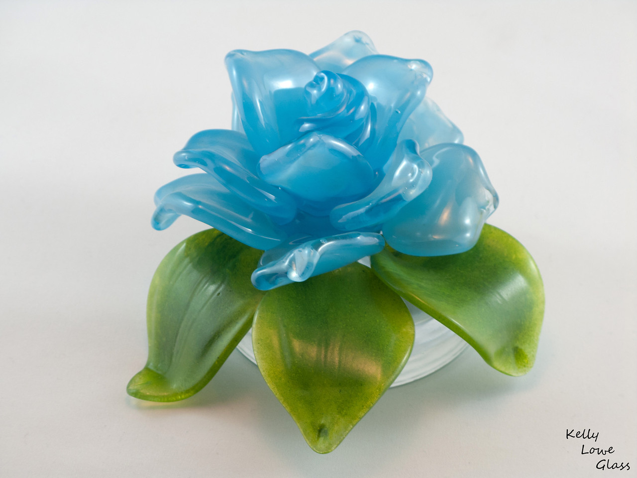 Glass flower with added sculpted glass leaves, mounted on a clear glass base.