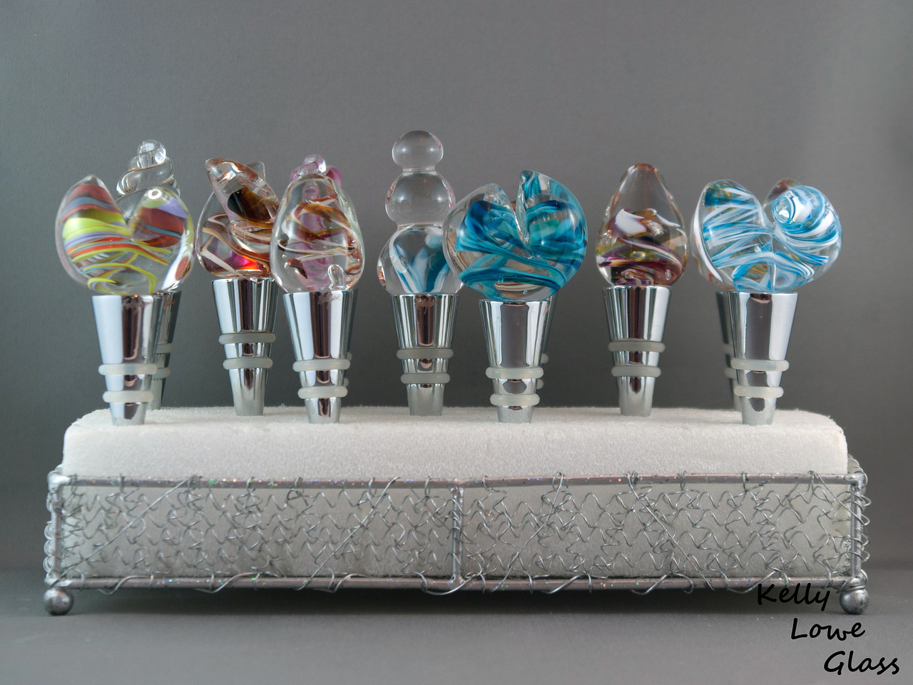 """Hand Sculpted Glass Wine Stoppers:  Each wine stopper consists of a hand sculpted glass top filled with a variety of colorful shapes and designs securely attached to a food grade stainless steel base. These wine stoppers are fully functional pieces of art, and will last for years, even decades, of regular use. As I sculpt the pieces entirely by hand no two wine stoppers will ever be exactly alike - making them a beautiful and unique addition to your table, your wine collection, as a special gift for the wine lover in your life, or as a colorful addition to celebrations such New Year's Eve, birthdays or anniversaries.  Each piece is discretely signed near the top of the base using a dremel: a diamond tipped engraving tool.  *Note - Due to there being a variety of wine stopper designs (see pictures #2 and #3) the figures given are a range from the smallest to the largest, with all others falling in between.   Base tip to top of glass: Approx 10-12cm (3.94"""" - 4.72"""") Widest point: Approx 3-5cm (1.18"""" - 1.97"""") Weight: approx 114-128g (0.25 - 0.28 lbs) Height of stopper w/o glass: 6.5cm (2.56"""")  (Return to the Special Occasions gallery)"""