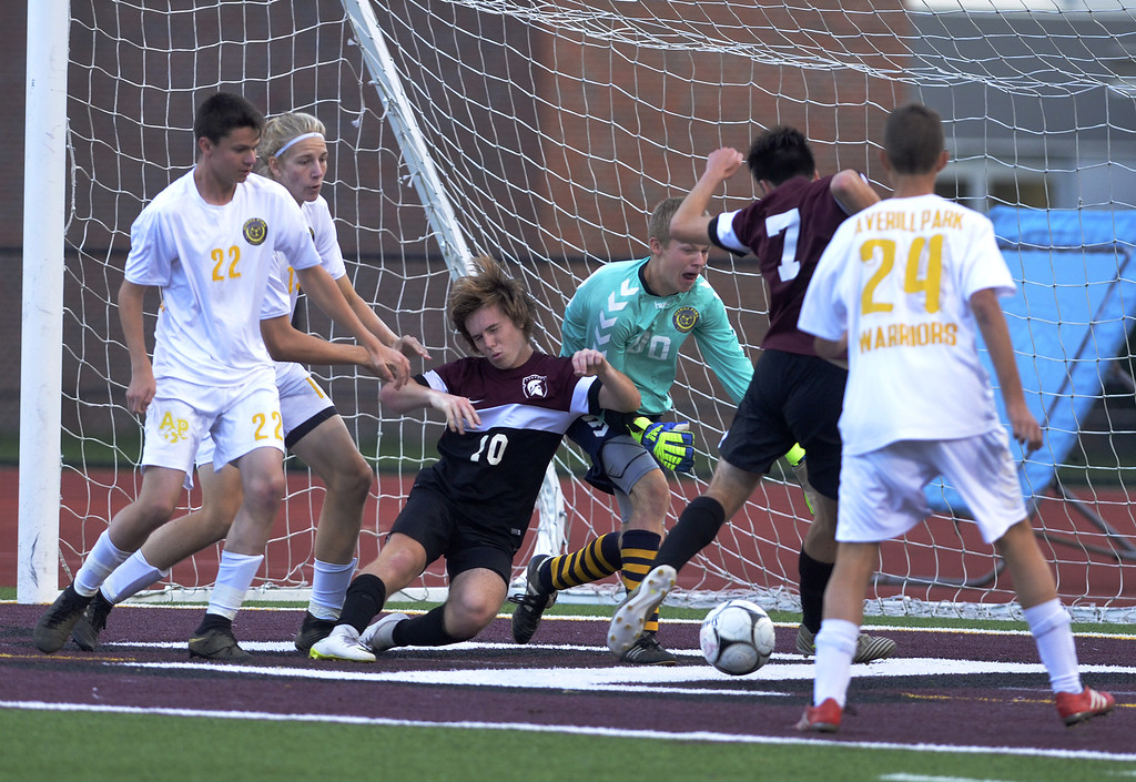 . Burnt Hills-Ballston Lake\'s Owen Muller (10) goes down in front of the boal as Averill Park goalie Eric Schumann (00) scrambles for the ball with Spartan Max Nemec (7) is coming in and WarriorAidan Millington (22) and Owen Joyce (20) supporting the play.