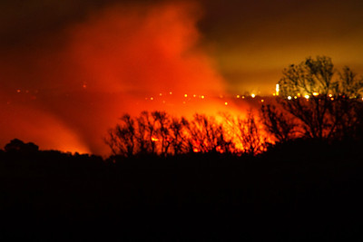Periodic controlled marsh-burning, a conservation practice that improves the quality of marsh vegetation, is usually done in the fall or winter.  This photo shows marshlands adjacent to Avery Island burning, with the lights from the Port of Iberia in the background.