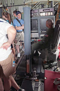 A Weather Officer, sitting at one of two weather stations, talks with the crowd about his job. In the foreground is the Drop Tube, where the Drop Drones are sent into the storm to send back information.