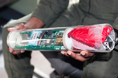 A close-up look at a Drop Drone. The Drop Drone is full of electronic data gathering equipment, that transmitts vital data back to the plane as it gently drops to the ocean. The red thing on the right is a tiny parachute that helps slow the fall of the Drop Drone from the plane.