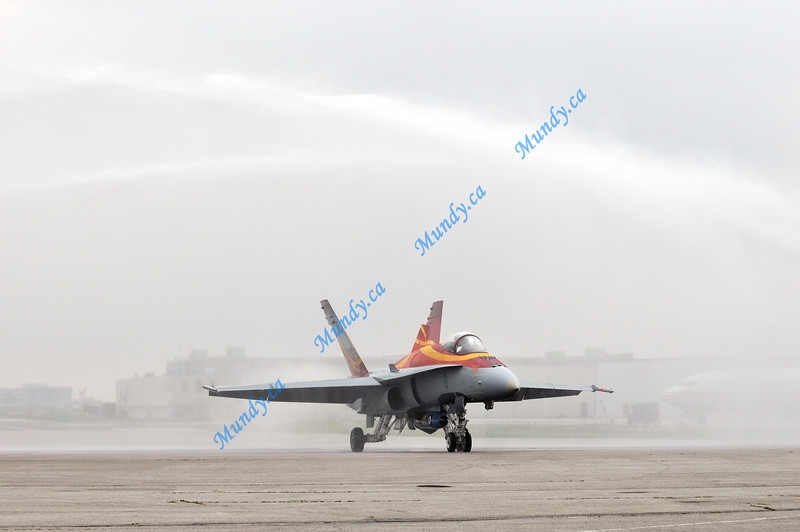 Water cannons shoot over the CF-18 as it taxis.