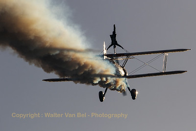 "The ""Breitling Wingwalkers"" - from Gloucestershire (UK) - were also present at the 2016 Sunset Airshow at Sanicole (EBLE). Here, one of the wing-walking girls is seen standing upside-down on the Boeing Stearman PT-17/R935 Kaydet (N74189; cn75-717) while flying straight into the direction of the setting sun."