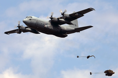 """Royal Netherlands Air Force cargo-drop demo: a C-130H (G-781; cn382-4781) performs a fly-by with the cargo-ramp opened and has just dropped 2 pieces of cargo (""""Luchtmachtdagen 2019"""" at Volkel AFB)."""