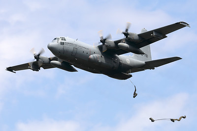 """Royal Netherlands Air Force cargo-drop demo: a C-130H (G-781; cn382-4781;""""Bob van der Stok"""") performs a fly-by with the cargo-ramp opened and has just dropped 2 pieces of cargo (""""Luchtmachtdagen 2019"""" at Volkel AFB)."""