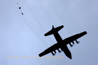 """Sunset paradrop by a Belgian Air Force C-130H Hercules. The para-jumper is from the Canadian team """"Skyhawks""""."""