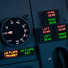 Dial gauge indicates the flaps setting, LE Flaps Transit shows leading edge flaps moving into position or 'In Transit'.  LE Flaps EXT indicates leading edge flaps fully extended.  Landing gear indicator lights on the right, three green indicates 'Down and Locked'.  737 NG flight deck instruments.