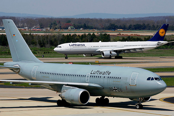 Luftwaffe A310 taxiing to parking; Lufthansa A330 in background rolling out on Rwy 19R, Washington Dulles Airport, VA (IAD).  April 16, 2008