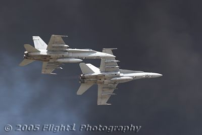 Two Hornets break for landing with smoke from pyrotechnics as a backdrop