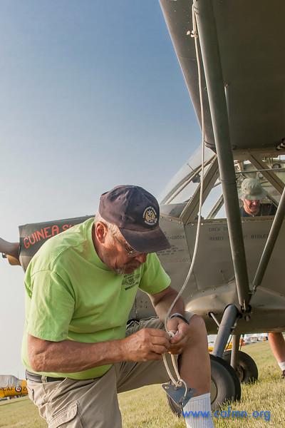 CAF member Bob Koelbl unfastens aircraft tie-downs while pilot John Schmidt preflights the L-5 cockpit.
