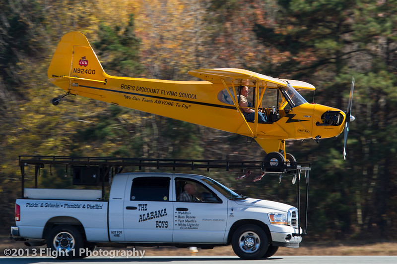 "Greg Koontz lands his Piper Cub on top of  ""The World's Smallest Airport"", his pickup truck."