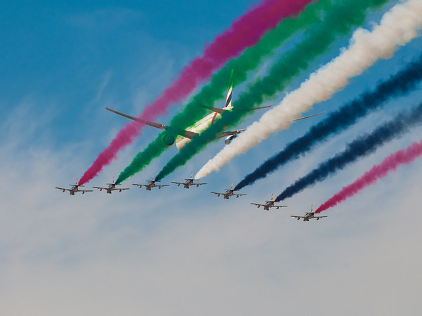 Al Fursan, the aerobatics demonstration team of the United Arab Emirates Air Force in Aermacchi MB-339NAT jet aircraft, escort an Emirates B777 over the Dubai Airport. Photo by: Stephen Hindley ©