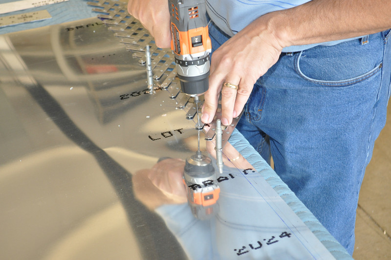 Drilling rivet holes in a very large sheet of aluminum wing skin. Carefully!