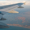 An airplane window view of wing after take off in during sunset.