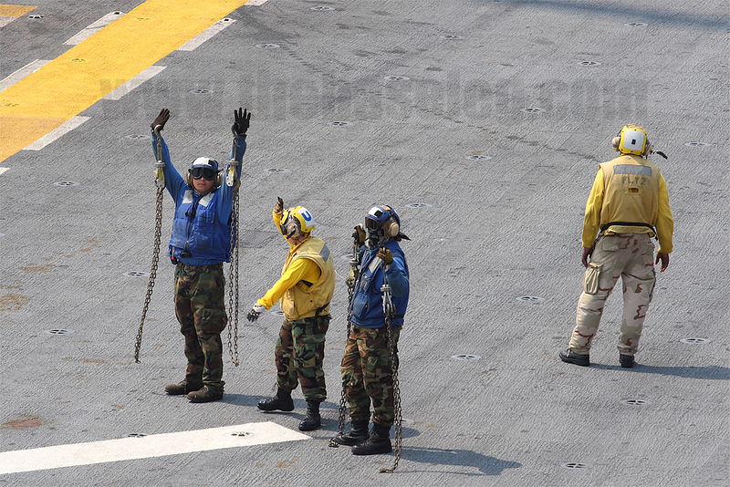 A pair of Plane Handlers (Blue jerseys) holds the helicopter's tie-down chains to indicate to the flight crew their aircraft is no longer tied-down while the Plane Director give directions.
