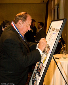 Clay Lacy signs the Legends poster.