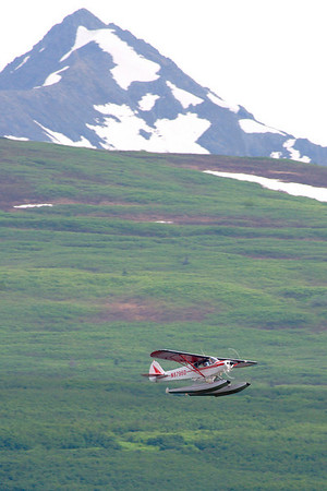 A Piper Cub, dwarfed by the terrain, over Chelatna Lake.