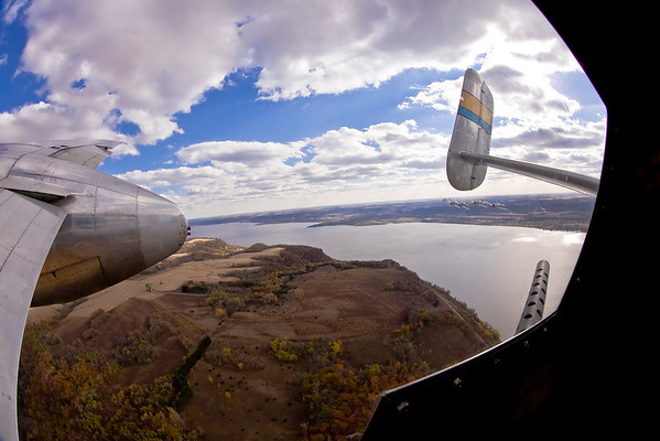 As seen from the right waist gun position on the B-25, the T-6 formation (visible under the vertical stabilizer) approaches over the Mississippi River.