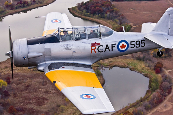 The CAF Harvard's natural metal finish and yellow markings provide a colorful contrast over the subdued colors of the Minnesota fall landscape.