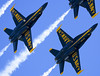 The Blue Angels in their F/A-18 Hornets in tight formation against a clear blue sky.