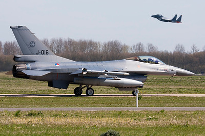 "Royal Netherlands Air Force F-16AM (J-016; cn6D-172), taxiing out to the active runway for another FF-2015 mission, while a two-seater USAF F-15D Eagle (85-0132; cn964/D058)  - from the 123rd Fighter Squadron ""Redhawks"" Oregon ANG - can be seen taking off in the background."