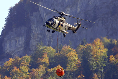 "Swiss Cougar (T-341, cn 2559/MIS026) returning to the drop-off zone with an emptied ""Bambi""-bucket, after a practise display at Axalp. Beautiful backdrop, as usual in Switserland (autumn colors of the trees lit by the afternoon sun and the rigid rocky mountain in the background)."