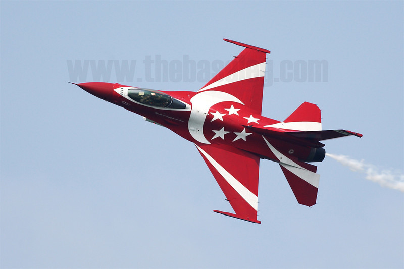 A Republic of Singapore Air Force Lockheed-Martin F-16C Fighting Falcon of the Black Knights aerobatics team shows off the national colours on its top fuselage in a knife-edge pass, Singapore Airshow 2014.