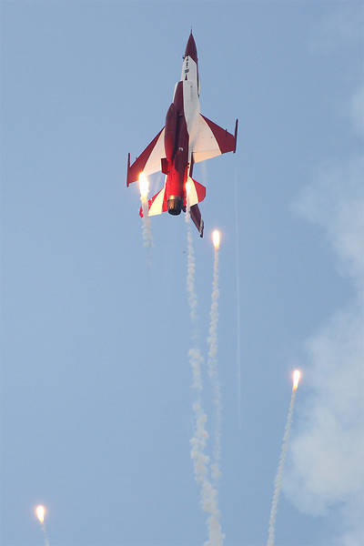 A Republic of Singapore Air Force Lockheed-Martin F-16C Fighting Falcon of the Black Knights aerobatics team releases flares as part of the team's display routine, Singapore Airshow 2014.